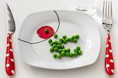 stock photo of impaler  - Peas on a plate with a glass of water - JPG