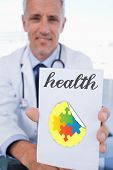 image of prescription pad  - The word health and portrait of a male doctor showing a blank prescription sheet against autism awareness jigsaw - JPG