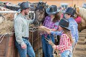 image of feeding horse  - cowboy family of four feed the horses hay - JPG