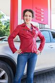 image of gasoline station  - woman posing on background of a car on gasoline station - JPG