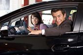 picture of showrooms  - Portrait of young couple sitting in a new car at showroom - JPG