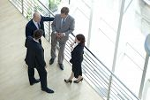 stock photo of conversation  - Businessmen and woman standing together by railing conversing - JPG