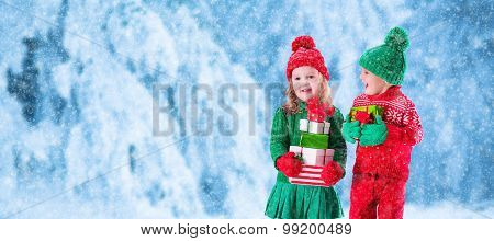 Kids With Christmas Presents In Snowy Winter Park