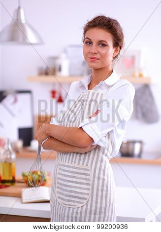 Smiling young woman standing  in the kitchen