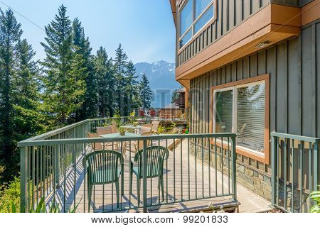 View of a stylish outdoor wooden floor patio with fantastic forest view.
