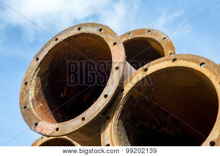Rusted industrial steel pipes on the blue sky background.