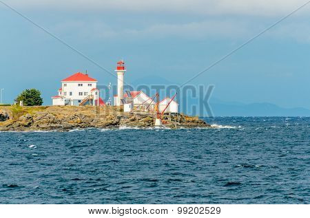 Lighthouse over a nice view of blue ocean and stone and rocky foreground.