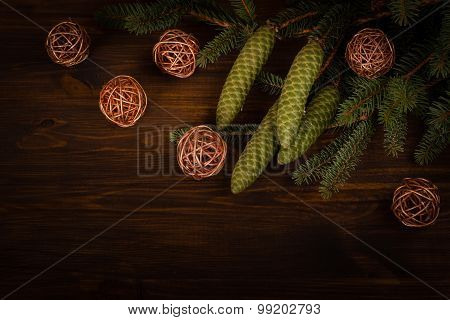 Spruce branch with cone and wicker balls on wooden planks