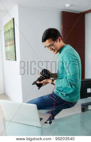 Asian Man Tethering Dslr To Laptop Pc Downloading Photo