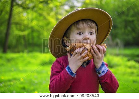 Cute Boy Eating A Croissant