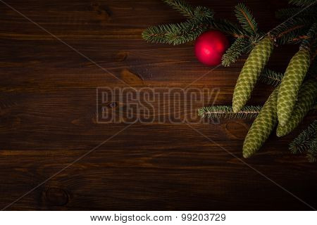 Spruce branch with cone and red ball on wooden planks