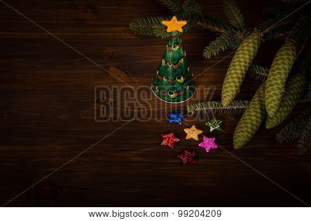 Spruce branch with cone and small Christmas tree on wooden planks