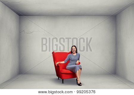 smiley woman sitting on red chair in empty grey room