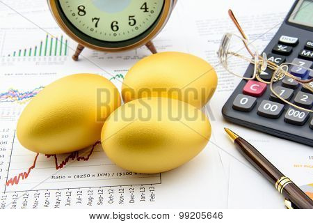 Three Golden Eggs With A Clock, Eye Glasses, A Calculator And A Pen On Business And Financial Summar