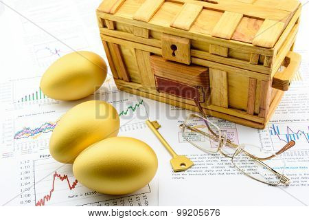 Three Golden Eggs And A Golden Key With A Wooden Chest On Business And Financial Reports.
