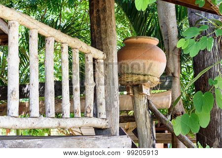 Earthen Water Jar In Front Of A Rustic Wooden House.