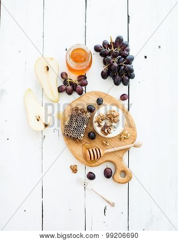Camembert cheese with grape, walnuts, pear and honey on oak serving board over white rustic wood bac