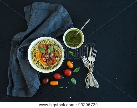 Pasta spaghetti with pesto sauce, basil, slow-roasted cherry-tomatoes in rustic metal bowl on dark g