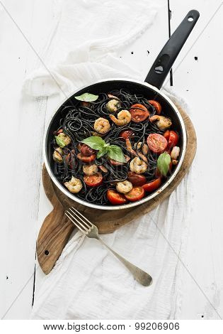Black pasta spaghetti with shrimps, basil, pesto sauce and slow-roasted cherry-tomatoes in cooking p