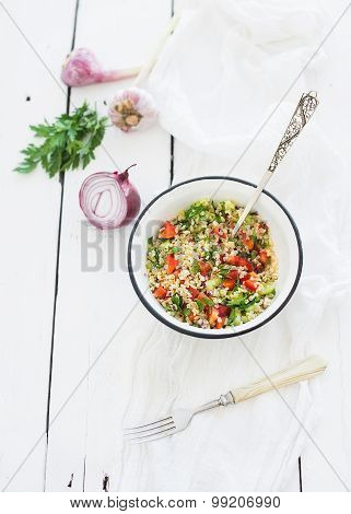 Healthy bulgur salad with paprika, red onion, parsley and garlic in rustic metal bowl. Vintage silve