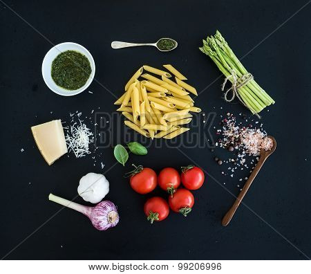 Ingredients for cooking pasta. Penne, green asparagus, basil, pesto sauce, garlic, spices, parmesan