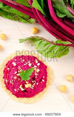 Beet hummus with peanuts and parsley on thin wafers