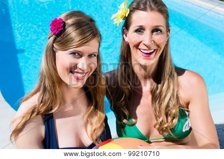 Two Women friends with water ball resting at pool tanning in the summer sun