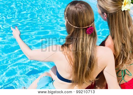 Friends sitting at swimming pool, view from behind, looking at the water