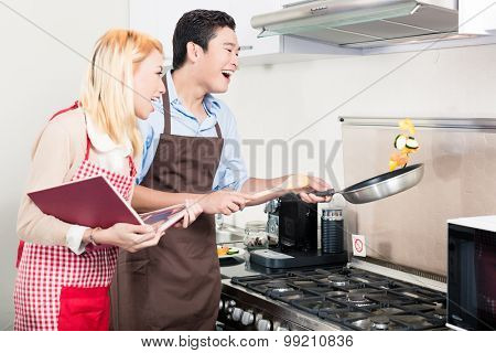 Asian couple cooking vegetables in frying pan