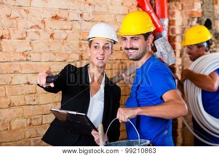 Builder and architect working on construction site discussing things still to do
