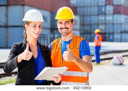 Manager with clipboard full of freight documents and worker on shipment yard in giving thumbs-up