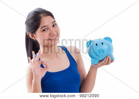 Happy woman pointing at piggy bank with showing ok sign isolated on white background