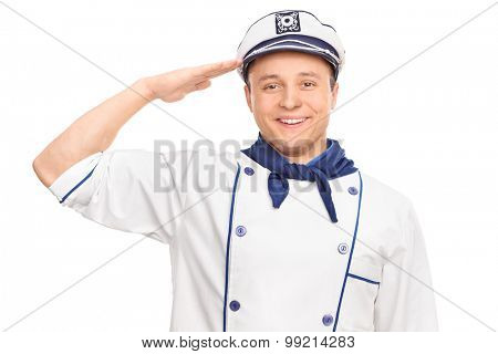 Cheerful young male sailor saluting towards the camera and smiling isolated on white background