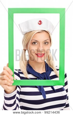 Vertical shot of a young female sailor holding a green picture frame and looking at the camera isolated on white background