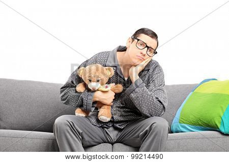 Sad man in pajamas holding a teddy bear seated on a sofa isolated on white