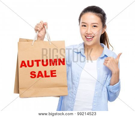 Woman with shopping bag and thumb up for showing autumn sale