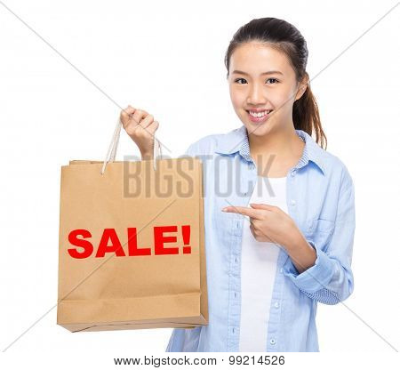 Asian woman finger point to shopping bag and showing a word sale!