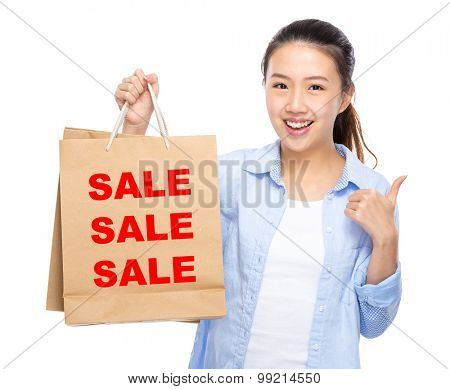 Woman with shopping bag and thumb up for showing three sale word