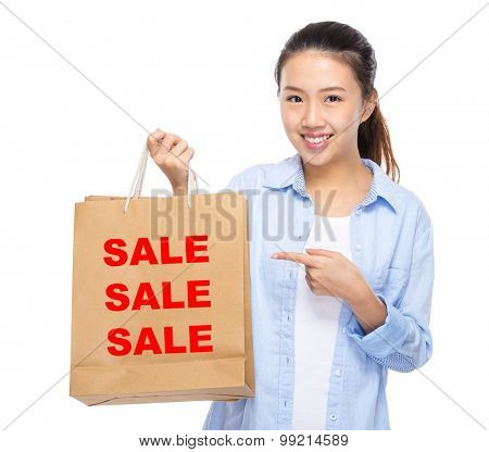 Asian woman finger point to shopping bag and showing three sale word