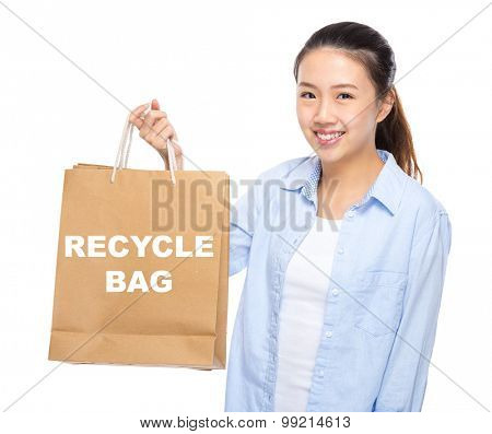 Young woman with shopping bag ans showing recycle bag