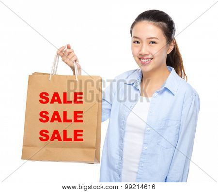 Young woman with shopping bag ans showing three sale word