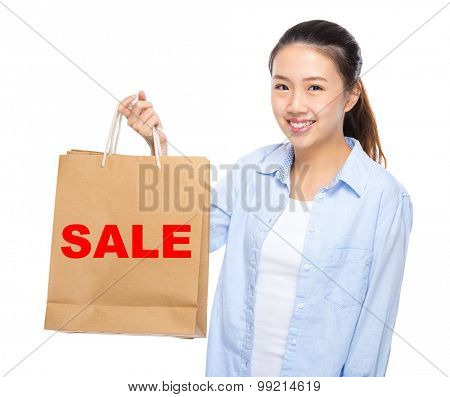 Young woman with shopping bag ans showing a word sale
