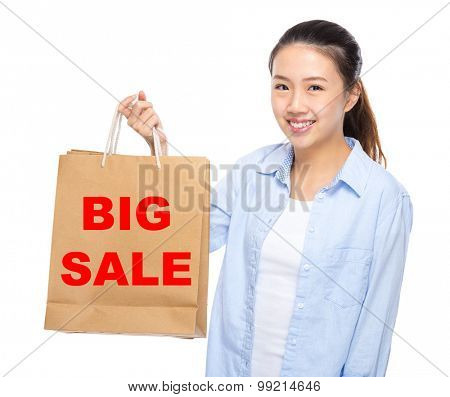 Young woman with shopping bag ans showing big sale