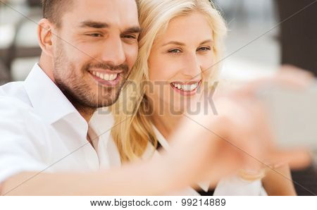 love, date, technology, people and relations concept - smiling happy couple taking selfie with smatphone outdoors
