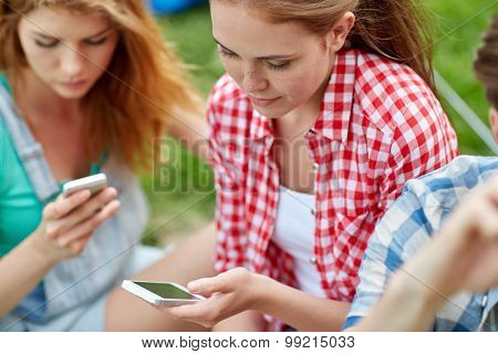 internet addiction, technology and people concept - group of friends with smartphone at camping