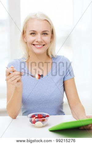 healthy eating, dieting and people concept - smiling young woman with tablet pc computer eating fruit salad at home