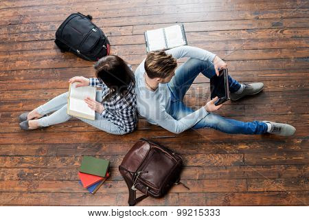 Girl reading a book and boy using a tablet leaning on each other on wooden floor having notebooks and bags around them.