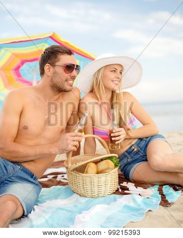 summer, holidays, vacation and happy people concept - happy couple with bottle drinks having picnic and sunbathing on beach under colorful parasol