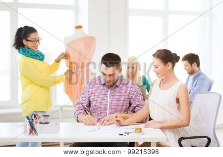startup, education, fashion and office concept - smiling designers drawing sketches and adjusting dress on mannequin in office