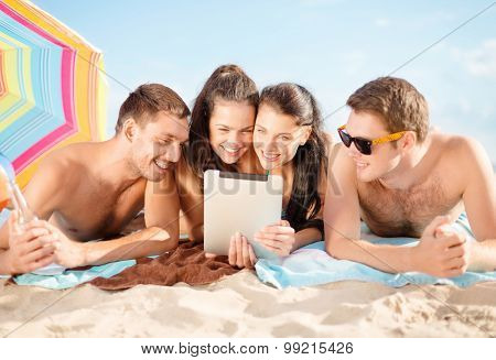 summer holidays, vacation, technology and people concept - group of happy friends with tablet pc computer sunbathing on beach